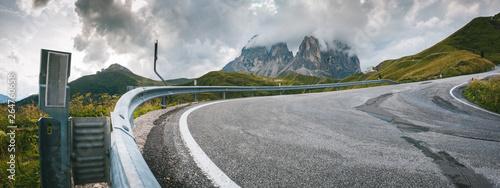Fotografie, Obraz  Serpentyna na asfaltowej górskiej drodze z barierami i szczytami gór w tle