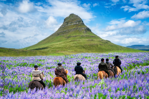 Fotografia Tourist ride horse at Kirkjufell mountain landscape and waterfall in Iceland summer