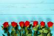 Leinwandbild Motiv roses line up on blue wood background with copy space