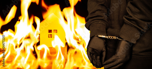 arsonist in handcuffs with a burning house on background Wallpaper Mural