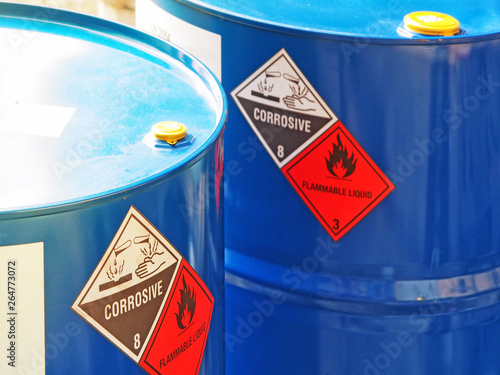 Fototapeta the close-up shot of blue color hazardous dangerous chemical barrels ,have warning labels of corrosive & flammable liquid in daylight on daytime. obraz