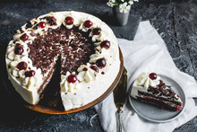 German, Delicious Black Forest Cake, With A Delicate White Cream, Cherries In Alcohol And Dark Chocolate On A Dark Stone Table Decorated With White Linen Fabric