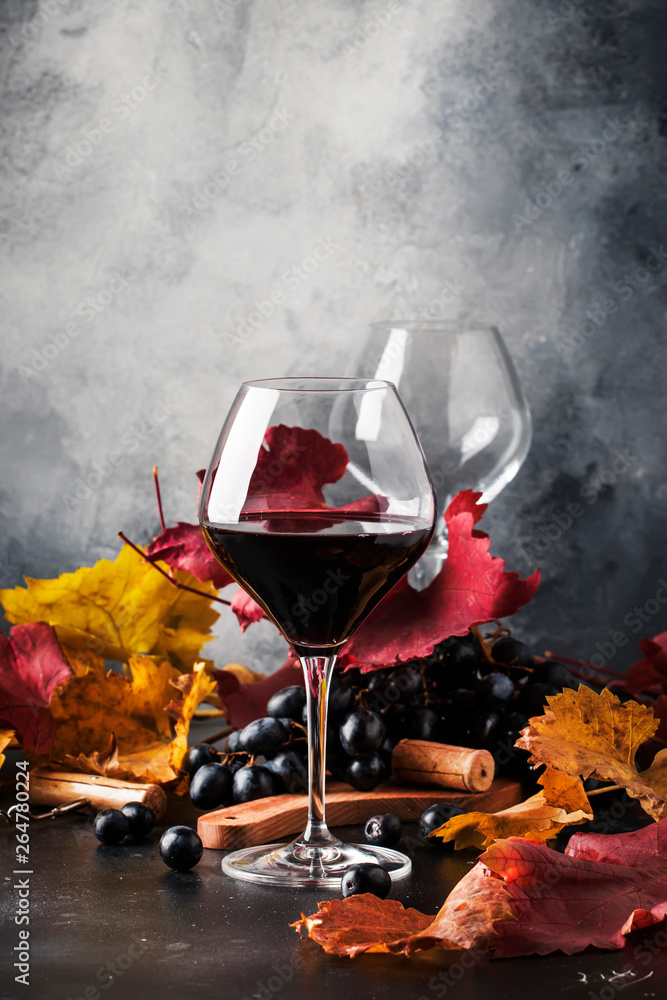 Fototapeta Red wine in wine glass, autumn still life with red and yellow leaves, wine tasting, copy space, selective focus