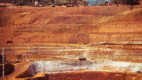 Red quarry with a huge stone with big trucks as toys Wallpaper Mural
