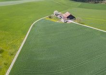 Aerial View Of Farm House In Remote Area In Rural Landscape In Switzerland.