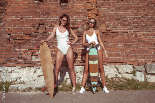 Photo Two girls of girlfriend summer city background brick wall white bathing suits baud, in hands skateboard, longboard