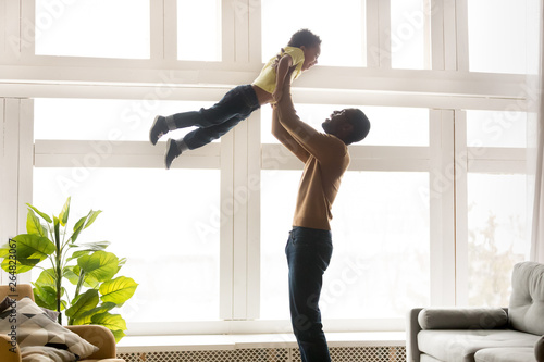 Fotografie, Obraz  Happy african father lifting up in air little son