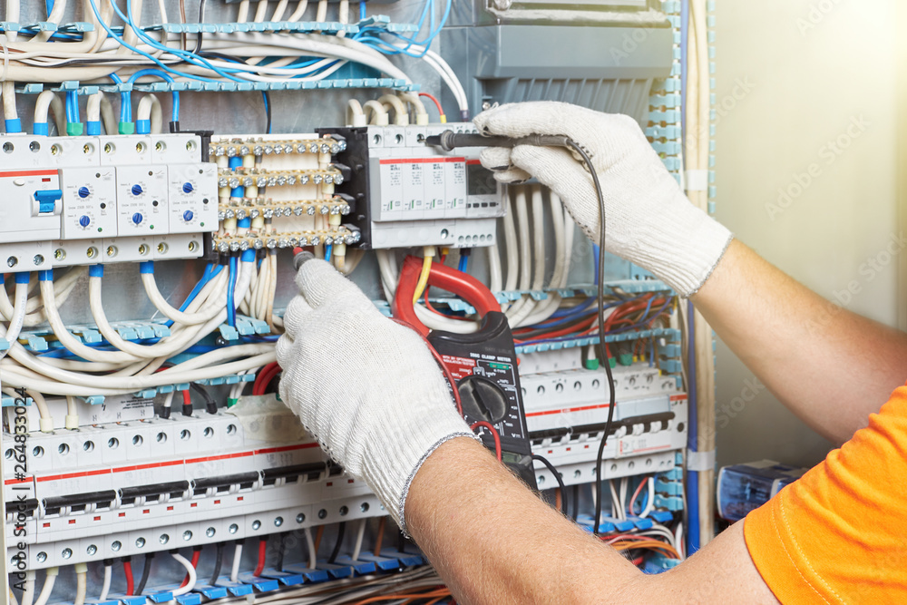 Fototapety, obrazy: A closeup of an electrical engineer working in a power electrical panel