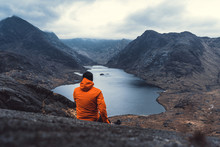 Young Man Sitting On Rock Looking Out Over Loch Coruisk Lake And The Cuillin Mountains. Listening To The Silence. Beautiful Moment The Miracle Of Nature.