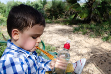 Cute Two Years Old Boy Eating Salty Sticks Snack In The Park