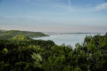 Fototapeta na wymiar montanhas e arvores verdes, com mar e um céu azul
