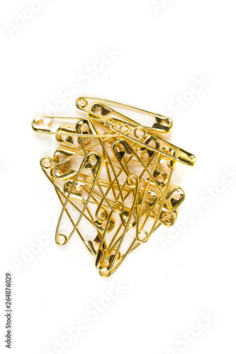 Stack of gold colored safety pins on a white background