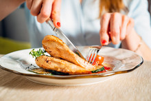 Woman Eating Grilled Chicken Breast