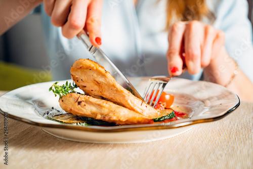 Fototapeta woman eating grilled chicken breast obraz