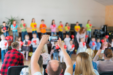 Performance by talented children. Children on stage perform in front of parents. image of blur kid 's show on stage at school , for background usage. Blurry