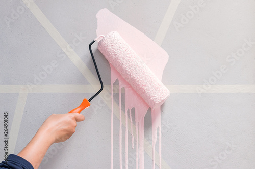 Foto  Young woman with the roller painting the wall in new house.