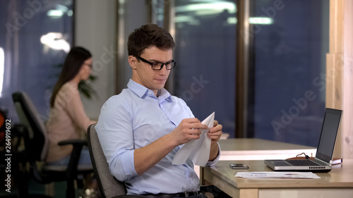 Playful male making paper plane in office, tired monotonous routine work, break