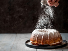 Woman's Hand Sprinkling Icing Sugar Over Fresh Muffin Cake. Powder Sugar Falls On Fresh Perfect Muffin Cake. Copy Space For Text. Ideas And Recipes For Breakfast Or Dessert