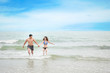 cheerful asian couple wearing blue bikini and black swimsuit. They having fun while holding hands and walking or running on the beach with love on honeymoon day during summer with clear blue sky