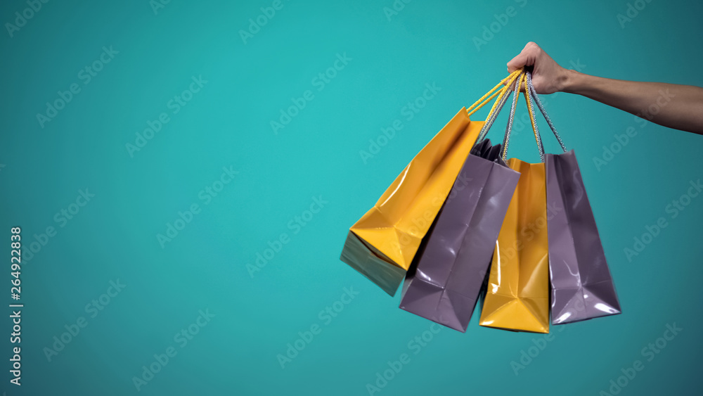 Fototapeta Female hand holding many colorful shopping bags on blue background, template