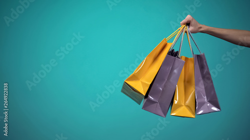 Female hand holding many colorful shopping bags on blue background, template