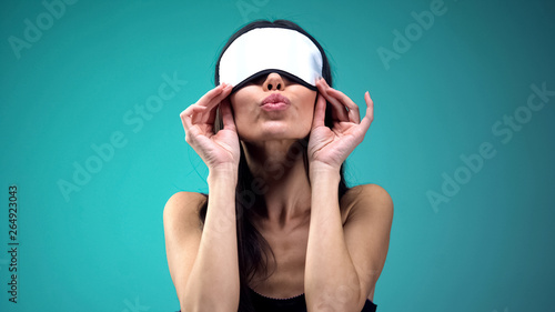 Woman in blindfold doing air kiss, flirting with admirer and having fun, joy Wallpaper Mural