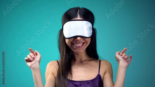 Fotografie, Obraz  Smiling woman in pajamas wearing blindfold on eyes, going to sleep, nighttime