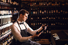 Elegant Wine Seller Holding A Bottle Of Wine And Reading Label In A Wine Store. Choosing Wine According To Its Origin Country And Vintage.