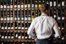 Backside Of Elegant Wine Seller Selecting Wine According To Its Origin Country And Vintage For Customers In Wine Shop