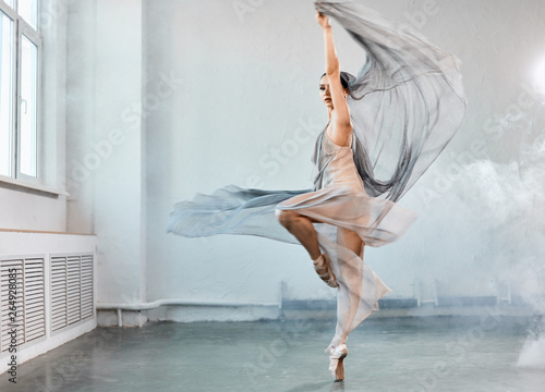 Photo Full size portrait of talanted ballet student woman wears grey fluttering scenic dress giving a performance on a final exam in light studio on white smoky background