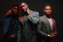 Group Of Three African Friends Dressed In Stylish Suits Posing Isolated In Studio Over Dark Background. Classmates Have Grown Up And Become Successful People. People, Fashion Condept