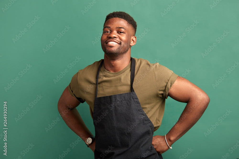 Fototapeta African male farmer with muscular hands and sportive body, dressed in apron smiling at camera with toothy smile over green background