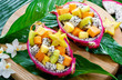 canvas print picture Exotic fruit salad served in half a dragon fruit on palm leaves