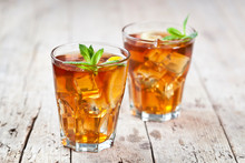 Two Glasses With Traditional Iced Tea With Lemon, Mint Leaves And Ice Cubes In Glass On Rustic Wooden Table.