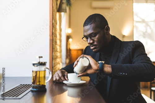 Deurstickers Ontspanning Young handsome dark-skinned businessman in a cafe with a cup of tea.