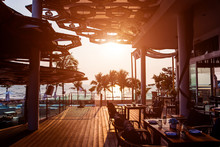 Beautiful Tropical Beach Restaurant With Palm Trees. Sunrises And Sunsets. Ocean.