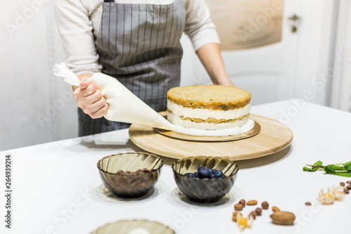 Photo  Confectioner with pastry bag squeezing cream on cake at kitchen