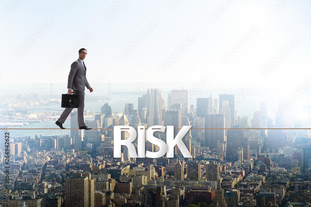 Fototapeta Businessman in risk concept walking on tight rope