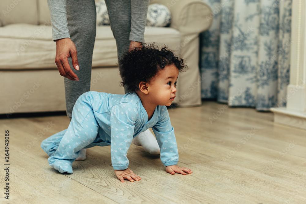 Fototapeta Side view of cute baby boy crawling on floor at home - obraz na płótnie