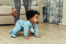 Side View Of Cute Baby Boy Crawling On Floor At Home