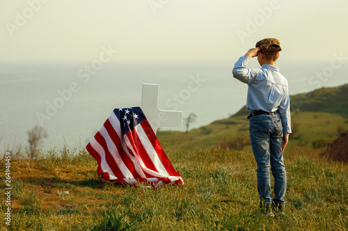 Photographie a young boy in a military cap salutes his father's grave on memorial day
