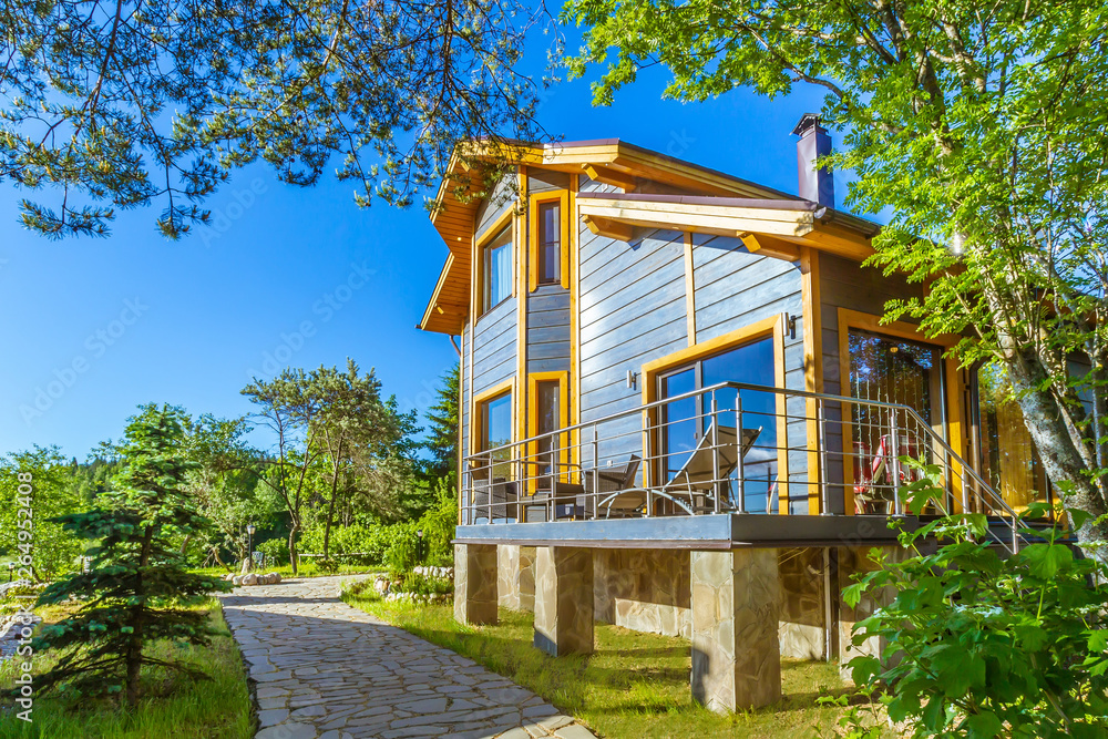 Fototapety, obrazy: Two-storey country cottage. Villa with open veranda. Vacation resort. Comfortable cottage for family rest. Cottages for rent outside the city. Tourist base. Recreation.