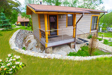 Small Country Villa. The House Is Surrounded By A Moat Paved With Stone. Ditch For Water Drainage. Home Decoration Stone. Stone Wall Decoration Of The House. Cottages For Rent In The Country.