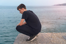 Young Man Crouching On A Pier,...