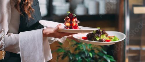 Fototapeta Waiter serving in motion on duty in restaurant. The waiter carries dishes obraz