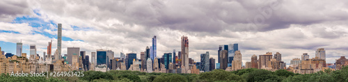 The beautiful New York City skyline with an interesting cloudy sky behind. Panorama of full skyline with all the famous towers and buildings.