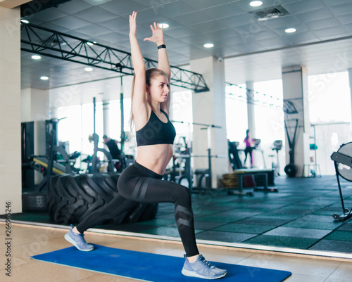 Photo Fitness blonde woman doing lunges legs with arms raised up in the gym