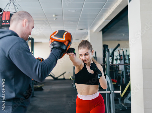 Fit blonde woman training punch with man trainer  at the gym