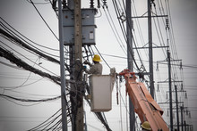 Electricians Wiring Cable Repair Services. Technician Checking Fixing Broken Electric Wire On Pole. Electricity Power Utility Worker In Crane Truck Bucket Fixes High Voltage Power Transmission Line.