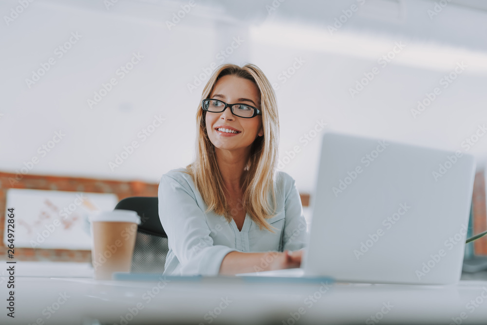 Fototapeta Positive businesswoman sitting with laptop and looking away